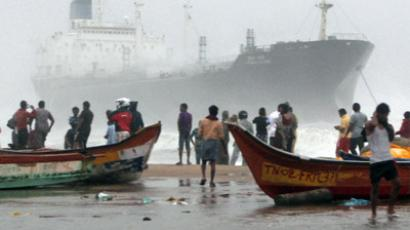INDIA, CHENNAI : Onlookers gather on the beach after the oil tanker ship Pratibha Cauvery ran aground off the coast in Chennai on October 31, 2012. The tanker ran aground off the city coast due to high winds before the landfall of Cyclone Nilam, a report said. AFP PHOTO/SESHADRI SUKUMAR