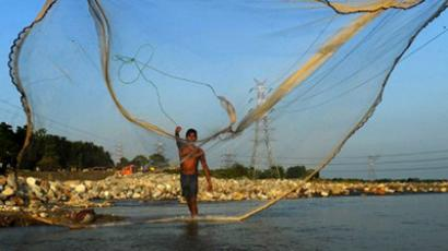 A fisherman throws his net into a river on the outskirts of Siliguri, India (AFP Photo / Diptendu Dutta)