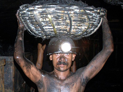 An Indian coal miner lifts a basket of coal as he works inside an underground tunnel of a mine owned by The Sinagareni Collieries Company Limited (SCCL) at Godavarikhani (AFP Photo/Noah Seelam/Files)