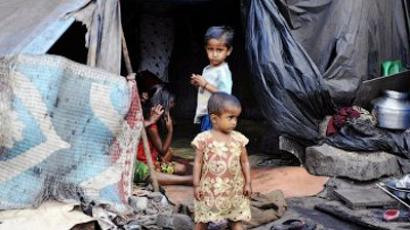 Young Indian children stand by a make-shift home by the roadside in Mumbai (AFP Photo / Sajjad Hussain)