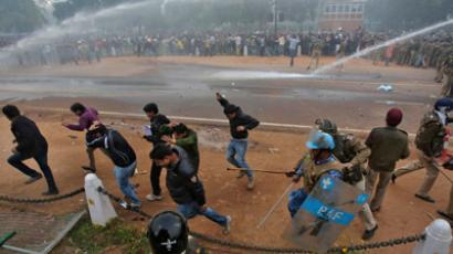 Police officers give chase and use water canons on demonstraters during a protest in front of India Gate in New Delhi December 23, 2012 (Reuters / Adnan Abidi)