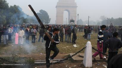 An Indian demonstrator holds up a burning plank, part of a barricade, during a protest calling for better safety for women following the rape of a student last week, in front the India Gate monument in New Delhi on December 23, 2012 (AFP Photo / Sajjad Hussain)