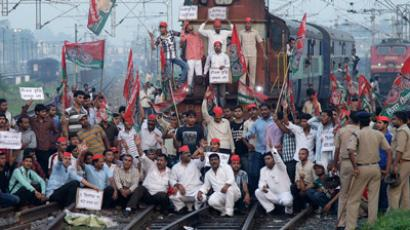 Demonstrators from the Samajwadi Party, a regional political party, shout slogans after they stopped a passenger train during a protest against price hikes in fuel and foreign direct investment (FDI) in retail, near Allahabad railway station September 20, 2012 (Reuters / Jitendra Prakash)