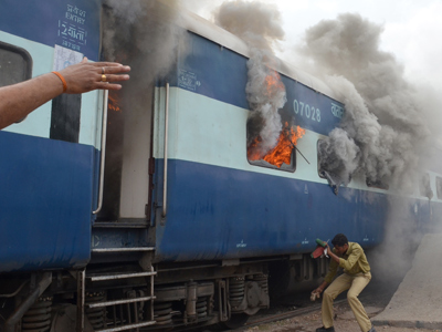 Jodhpur : An Indian railways staff member covers his face as he approaches a train car on fire near the Jodhpur railway station in Jodhpur on July 13, 2012 (AFP Photo / STR)