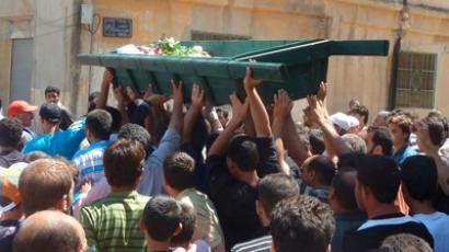 Syrian residents carry the body of a man whom protesters say were killed by forces loyal to Syria's President Bashar al-Assad, during his funeral in Huola near Homs June 12, 2012 (Reuters/Shaam News Network/Handout)