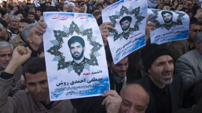Worshippers carry portraits of Iranian nuclear scientist Mostafa Ahmadi-Roshan during his funeral on January, 13  (Reuters / Morteza Nikoubazl)