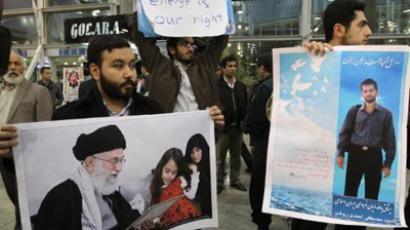 ranian students hold a poster of assassinated nuclear scientist Mostafa Ahmadi-Roshan (R) and a picture of the family of killed nuclear scientist Dariush Rezaei with Iran's supreme leader Ayatollah Ali Khamenei as they protest at the Imam Khomeini airport in Tehran on January 29, 2012 during the arrival of the International Atomic Energy Agency (IAEA) inspectors (AFP Photo / Atta Kenare)