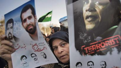 A worshipper holds an anti-U.S. President Barack Obama poster and portraits of killed Iranian nuclear scientists during the funeral for nuclear scientist Mostafa Ahmadi-Roshan, who was killed in a bomb blast in Tehran on January 11, after Friday prayers January 13, 2012. (REUTERS/Morteza Nikoubazl)
