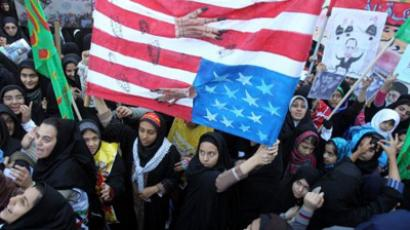 Iranian women hold up an upside down US flag outside the former US embassy in Tehran on November 4, 2011 (AFP Photo / Atta Kenare)