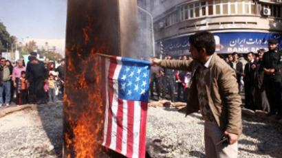 Iranian men burn a US flag outside the former US embassy in Tehran (AFP Photo / ATTA KENARE)