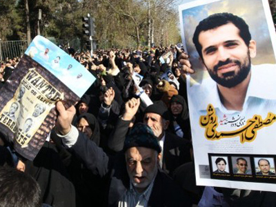 Iranians hold a portrait of assassinated nuclear scientist Mostafa Ahmadi-Roshan (AFP Photo / Atta Kenare)