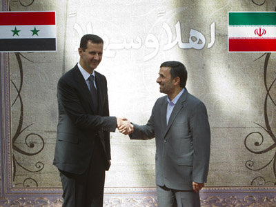 Iranian President Mahmoud Ahmadinejad (R) shakes hands with his Syrian counterpart Bashar al-Assad (Reuters/Morteza Nikoubazl)