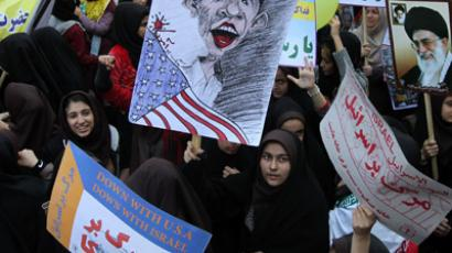 Iranian demonstrators hold anti-US and Israel slogans, a cartoon of US President Barack Obama (L) and a portrait of supreme leader, Ayatollah Ali Khamenei (R) outside the former US embassy in Tehran on November 2, 2012, during a rally to mark the 33rd anniversary of seizure of the US embassy which saw Islamist students hold 52 diplomats hostage for 444 days. (AFP Photo/Atta Kenare)