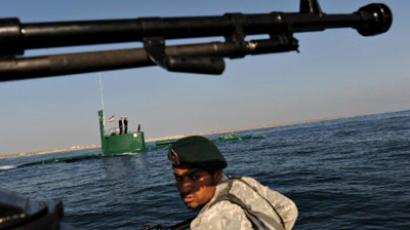 "Iran, Hormuz: An Iranian Army soldier stands guard on a military speed boat, passing by a submarine during the ""Velayat-90"" navy exercises in the Strait of Hormuz in southern Iran on December 28, 2011 (AFP Photo / Ali Mohammadi)"
