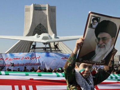 An Iranian boy holds a portrait of supreme leader, Ayatollah Ali khamenei as he walks past a replica of the captured US RQ-170 drone on display next to the Azadi (Freedom) tower during the 33rd anniversary of the Islamic revolution in Tehran on February 11, 2012 (AFP Photo/Atta Kenare)