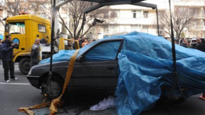 Iranian security forces inspect the site where a magnetic bomb attached to a car by a motorcyclist exploded outside a university in Tehran on January 11, 2012 (AFP Photo / IIPA / Sajad Safari)