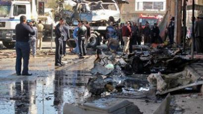Iraqis inspect the site of a car bomb in the central town of Hilla, south of the capital, on March 20, 2012, which killed two people and wounded 31 others. (AFP Photo / STR)