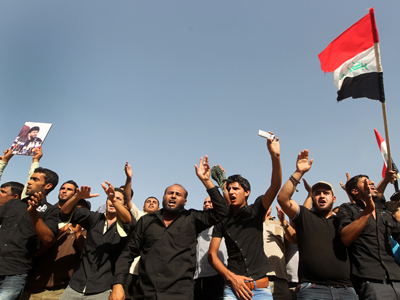 Hundreds of Iraqi protesters chant slogans as thehold a national flag during a demonstration in Baghdad on June 20, 2012 to protest against the action by the government after shutting down the offices of Al-Baghdadia, a Cairo based independent Iraqi-owned Arabic-language satellite channel, in Iraq (AFP Photo / Ahmad  Al-Rubaye)