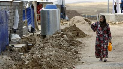 A Syrian-Kurdish refugee woman carries a container as she walk along a road in the Domiz refugee camp, 20 km southeast of Dohuk city, in northern Iraq, on July 17, 2012.  (AFP Photo/Safin Hamed)