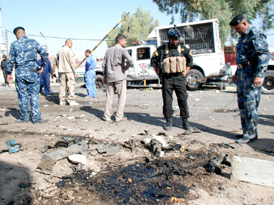 Iraqi security personnel stand at the site of a bomb attack in Kut, September 30, 2012 (Reuters / Jaafer Abed)