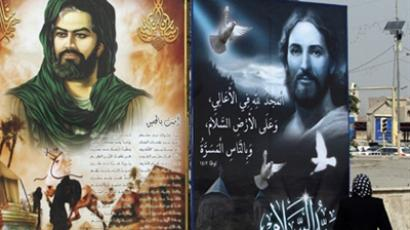 An Iraqi woman walks past posters of Jesus Christ (R) and Shiite Imam Hussein in the center of Baghdad, Iraq (AFP Photo / Ali Al-Saadi)