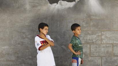 Boys stand next to a damaged wall of a house, where a girl was killed when a rocket hit it, in the Iraqi border town of al-Qaim in Anbar province, September 8, 2012. (Reuters/Thaier al-Sudani)