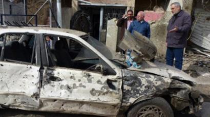 Iraqis inspect a destroyed car following a blast in central Baghdad (AFP Photo / Sabah Arar)