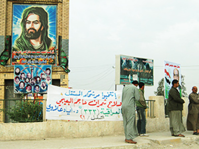 Under the portrait of Imam Husayn ibn Ali ibn Abi Talib, there are photos of the shahids killed by American troops during the uprising of the Shiite Mahdi Army in 2004