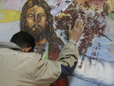 An Egyptian Christian mourns as he stands next to a blood-stained painting of Jesus Christ (AFP Photo / Mohammed Abed)