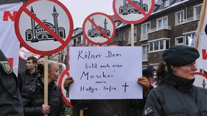 "Germany, Cologne: Members of the group ""Pro Cologne"" hold a poster reading ""Cologne's Cathedral also a mosque soon, as Hagia Sophia"" as they demonstrate against the DITIB Central Mosque under construction of the Turkish Community in Cologne Ehrenfeld, western Germany, on February 2, 2011. (AFP Photo / Patrick Stollarz)"