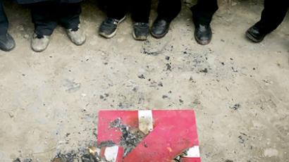 Iranian students stands next to a burnt Danish flag in front of the Danish embassy during a protest over the publication of cartoons depicting Prophet Mohammad in Tehran, 13 February 2006 (AFP Photo)