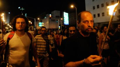 Israelis, holding torches, attend a demonstration in Tel Aviv on July 21, 2012, in memory of Moshe Silman (AFP Photo / David Buimovitch)