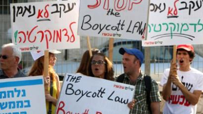 "Jerusalem : Israeli left wing activists hold signs as they demonstrate against the suggested ""boycott law"", in front of the Justice ministry in east Jerusalem on July 10, 2011. (AFP Photo / Ahmad Gharabli)"