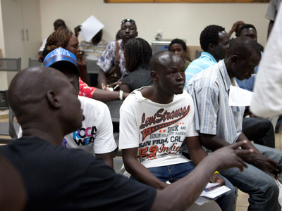 South Sudanese migrants receive instruction at the Immigration population Authority office in Eilat as they prepare to return to South Sudan, in southern Israeli city of Eilat.(AFP Photo / Menahem Kahana)
