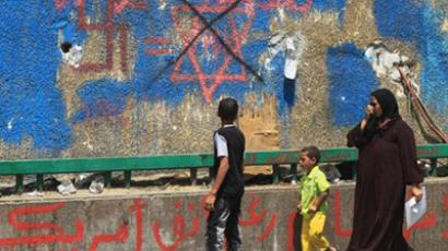 "Egyptians walk past graffiti reading ""Down with Israel"" near the Israeli embassy in Cairo (AFP Photo / Khaled Desouki)"