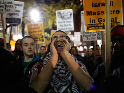 People hold signs as they chant during a Pro-Palestinian protest against Israel across the street from the Israeli consulate in New York Novemer 16, 2012 (Reuters / Carlo Allegri)