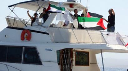 "Activists show Palestinian flags onboard a ship flying the French flag named ""Dignité - Al Karama"" (Dignity - Al Karama) as it sails off town of L'Ile Rousse in the French Mediterranean island of Corsica on June 25, 2011 to join the new pro-Palestinian aid flotilla which plans to break the Israeli-imposed blockade of Gaza (AFP Photo / Murielle Kasprzak)"