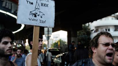 Left-wing protestors raise a sign picturing a member of the Klu Klux Klan (KKK) in opposition to a right-wing demonstration against African migrants in the city of Tel Aviv on May 30, 2012 (AFP Photo / David Buimovitch)