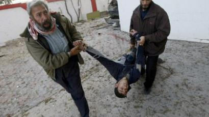Palestinian men pull a man injured in the Zeitun district of Gaza City following Israeli strikes on January 12, 2009. (AFP Photo / Mahmud Hams)