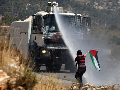 A Palestinian woman waves her national flag in front of an Israeli military water cannon during a demonstration in the West Bank village of Nabi Saleh to protest against the confiscation of Palestinian land to expand the nearby Jewish settlement of Halamish (AFP Photo / Abbas Momani)