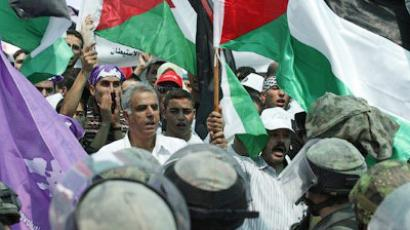Palestinian Muslims waving national flags protest against Israeli security forces near the Qalandia checkpoint in the West Bank after being prevented from crossing to Jerusalem on August 26, 2011 (AFP Photo / Abbas Momani)