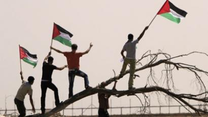 Palestinians wave their national flag as they protest against the Israeli blockade at the Al-Maghazi refugee camp near the border with Israel in central Gaza Strip. (AFP Photo / Mahmud Hams)