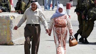 An elderly Palestinian couple walks near Israeli soldiers at the Israeli-manned Qalandia checkpoint between Jerusalem and the West Bank city if Ramallah, on May 20, 2011 (AFP Photo / Getty Images)