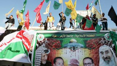Palestinian students wave the flags of the Hamas movement (green), the Fatah party (yellow) and the Popular Front for the Liberation of Palestine (red) as they celebrate the political unity deal between Gaza rulers Hamas and the rival party Fatah during a rally at Al-Azhar University in Gaza City on May 8, 2011 (AFP Photo / Mahmud Hams)