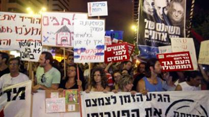 Israelis hold banner as they march in the centre of the coastal city of Tel Aviv on July 30, 2011, to protest against rising housing prices and social inequalities in the Jewish state (AFP Photo / Jack Guez)