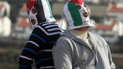 Palestinian protesters seen as they wear a head mask painted in the colors of the Palestinian flag during a weekly protest against a nearby Jewish settlement in the West Bank village of Nabi Saleh, near Ramallah February 3, 2012 (Reuters / Stringer)