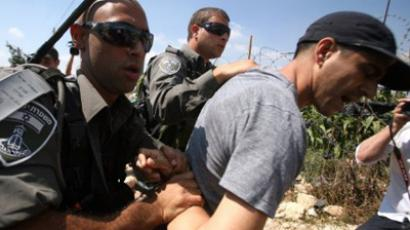Israeli soldiers detain a Palestinian demonstrator during a protest against Israel's controversial separation barrier in the village of Maasarah near the West Bank city of Bethlehem on September 2, 2011 (AFP Photo / Musa Al-Shaer)