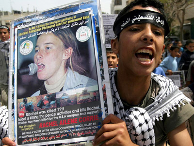 A member of the children's Palestinian parliament holds up a placard showing a picture of Rachel Corrie during a demonstration to mark the second anniversary of her death in the Rafah refugee camp in the southern Gaza Strip 13 April 2005. (AFP Photo/Said Khatib)