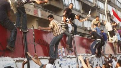 Some hundreds of Egyptian activists demolish a concrete wall built around a building housing the Israeli embassy in Cairo, Egypt, to protect it against demonstrators, as they raise their national Friday, Sept. 9, 2011 (AFP Photo / Getty Images)