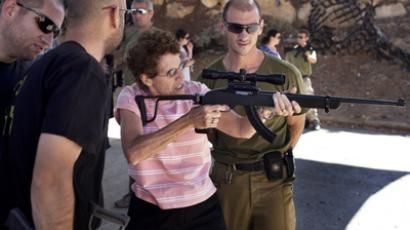 Israeli soldiers supervise an American tourist firing a gun as she participates in an introductory course to handling firearms at the Caliber 3 shooting range located near the West Bank settlement of Efrat (AFP Photo / Menahem Kahana)